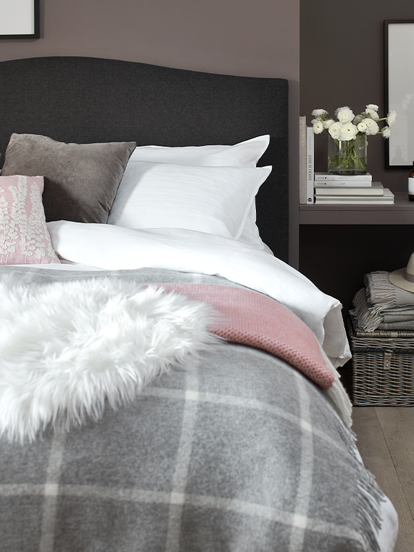 Witney grey tweed upholstered kingsize bed, fabric bed, luxury bedding, fern fronds cushion, cashmere throws, faux flowers, bedside table